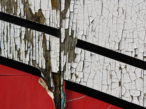 A wall with cracked and peeling paint indicates that it's time for exterior painting.