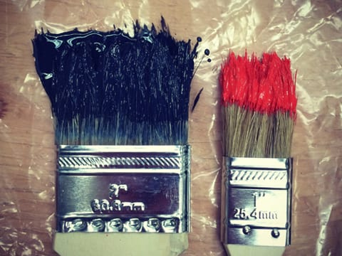 Two paint brushes stained with different color paint. The two inch brush on the left is stained with black paint, and the one inch brush is stained with red paint.