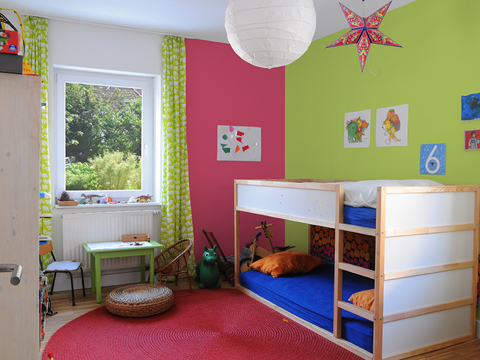 A small kid's room with a bunk bed, green and pink walls, a white window, green and white curtains and lots of toys.