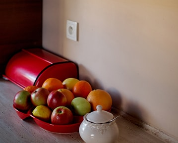 Kitchen counter with a bowl of apples on top in front of a peach colored interior wall.