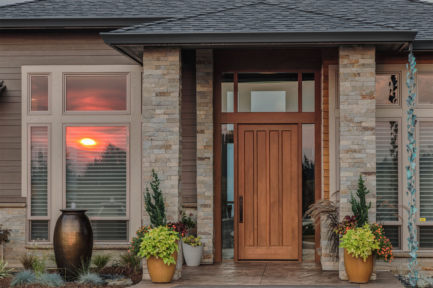 Entrance of a house with light brown painted siding and stained wooden doors.