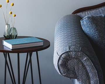 A fragment of a blue couch and a side table in front of a freshly painted light grey wall.