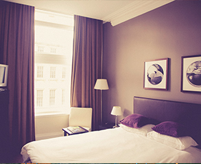 A hotel room painting project. The walls have been painted purple, matching purple curtains hang on the window, creating a nice contrast to the white bed sheets.