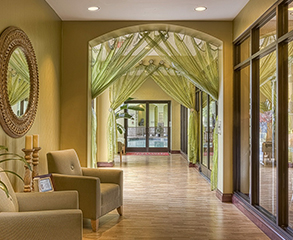 Hotel lobby painting project. The walls are painted yellow to match the beige colored furniture, light green curtains cover the arcs, and the large wood frame windows open a view into the yard.