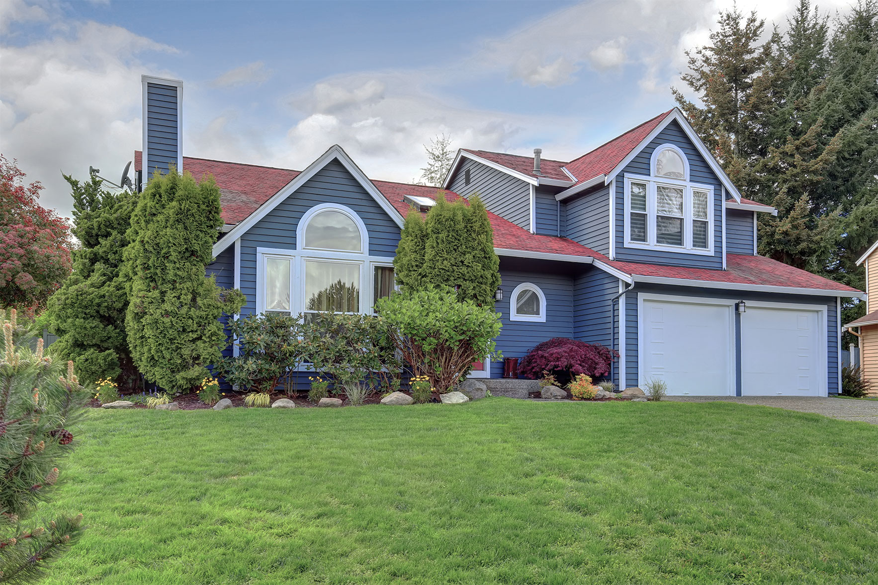 A house with blue exterior paint, bright red roof, large white windows and tidy landscaping.