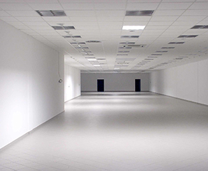 Inside of a large industrial facility. The walls and ceiling are painted white, the floors coated with epoxy.