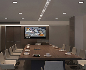 A modern conference room with grey and brown painted walls, large wood doors, a flat screen TV on the wall, and a large dark brown wood conference table with white cups on it and white color chairs around it.