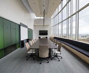 A clean and bright conference room in an office with a flat screen TV, long conference table, 16 chairs around it and big windows that allow sunlight in.