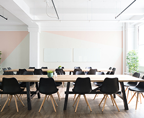 A large office space with white and pink colored walls, large windows, two long wood tables and a lot of black chairs around them.