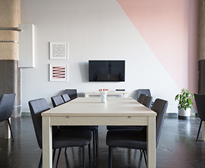 A modern office space with white and pink painted walls, large wood table with six chairs in the center, a flatscreen TV and two small paintings on the wall, and a plant in the corner of the room.