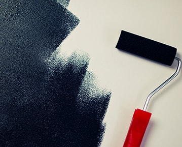 Painting over a white wall with a paint roller and black paint.