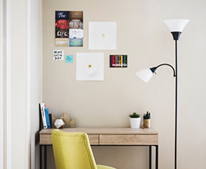 A beige home office in a condo. The walls are painted a clean white, there are several pictures hanging above the small wood desk, there are some books and two plants on it, a yellow chair is next to the desk, and there is a white lamp right to the desk.