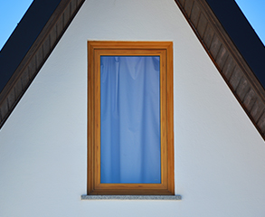Closeup of a white townhouse exterior with a big window that's covered with blue curtains.