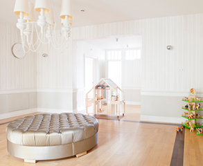 White interior with light wood floors, a large ottoman in the center of the room and kid's toys.