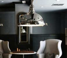 Luxury interior with two grey armchairs, a table with a chess board, large metal lamps and and a modern mirror hung on a half grey and half black painted wall.