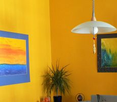Corner of a mustard colored room with two paintings hanging on the adjoining walls, a ponytail palm on the table and a large hanging light.