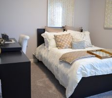 Small bedroom with a black, decorated twin bed, black desk with white and gold colored decorations on top and a white chair next to it, gray carpet and gray painted walls.
