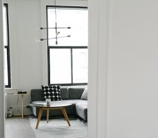 White interior of loft in Chicago, with large dark framed windows, grey couch and a coffee table in the center of the room.